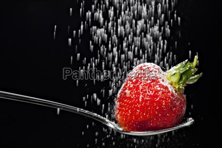 icing sugar falling on a strawberry