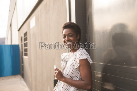 smiling african american woman holding cell