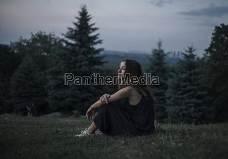 pensive caucasian woman sitting in field